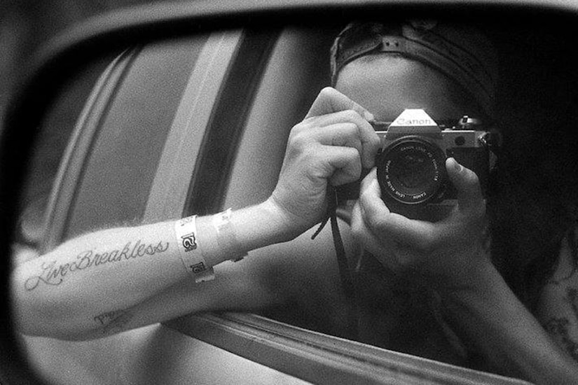 Photographer self-portrait shot in a car's side mirror.