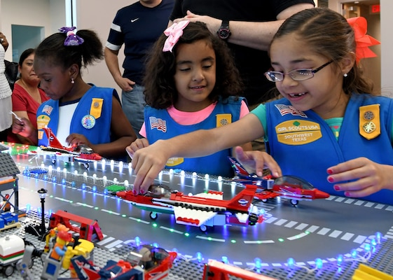 "San Antonio-area Girl Scouts visit the 90th Cyberspace Operations Squadron ""Bricks in the Loop"" at Joint Base San Antonio-Lackland for a tour April 19, 2019. ""Bricks in the Loop"" mimics an Air Force installation with items such as a fire station, police station, airport, jets and tanker trucks, all used to simulate real-world cyber systems in training cyber operators."