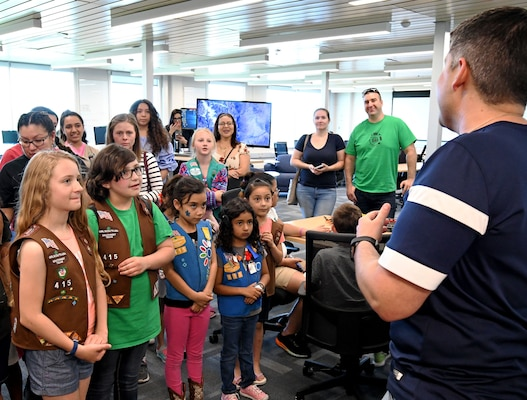 "Christopher De La Rosa, 90th Cyberspace Operations Squadron cyber modeling and simulation environments lead, welcomes Girl Scouts to a ""Bricks in the Loop"" tour at Joint Base San Antonio-Lackland April 19. ""Bricks in the Loop"" mimics an Air Force installation with items such as a fire station, police station, airport, jets and tanker trucks, all used to simulate real-world cyber systems in training cyber operators."