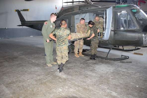 Air advisors from the 571 Mobility Support Advisory Squadron, and Guatemalan air force students practice loading a litter patient into the partner nation's UH-1 aircraft during a mobile training mission at Aurora Air Base in Guatemala. The students are part of the first aeromedical evacuation unit in the Guatemalan air force. (Courtesy Photo)