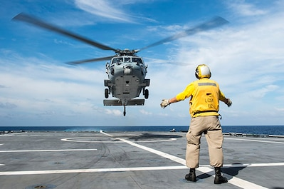 161014-N-MW990-294 SOUTH CHINA SEA (October 14, 2016) Chief Petty Officer Jed May, a native of Steamboat Springs, Colorado, directs an MH-60S helicopter departing littoral combat ship USS Coronado (LCS 4). Currently on a rotational deployment in support of the Asia-Pacific Rebalance, Coronado is a fast and agile warship tailor-made to patrol the region's littorals and work hull-to-hull with partner navies, providing 7th Fleet with the flexible capabilities it needs now and in the future. (U.S. Navy photo by Petty Officer Second Class Michaela Garrison/Released)