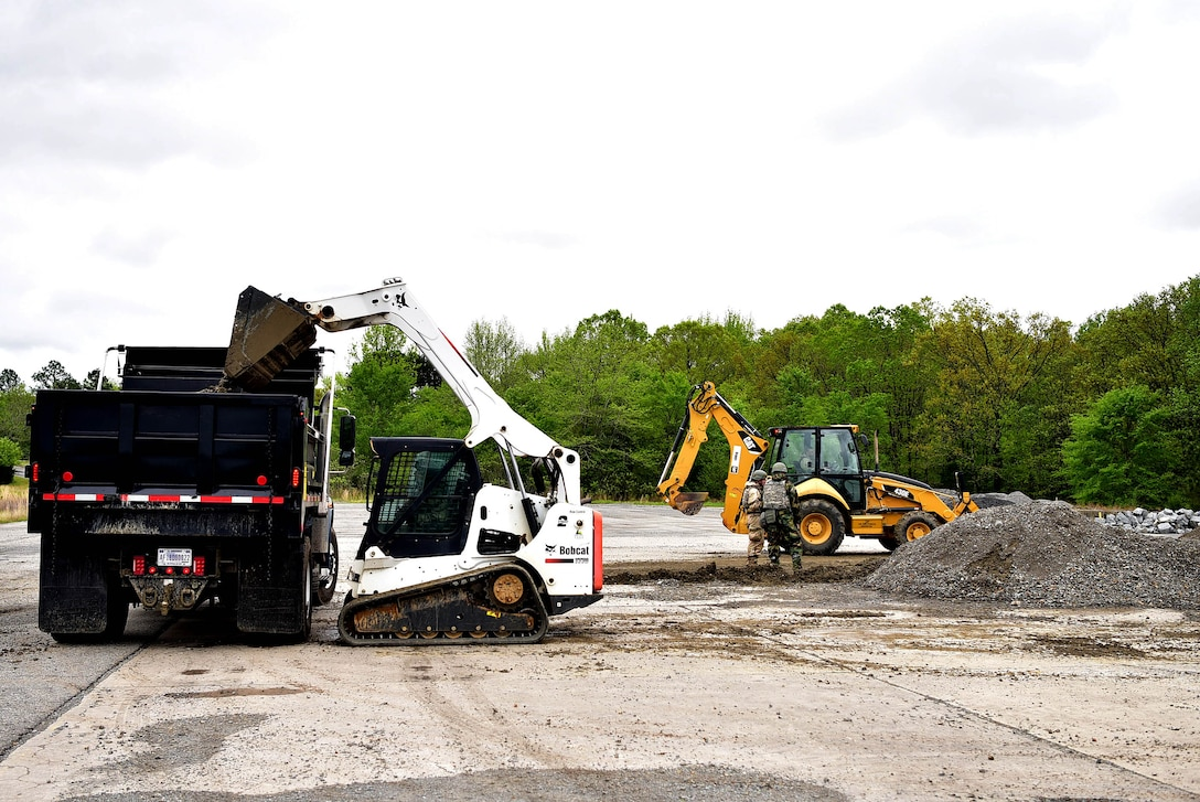 Two pieces of machinery pick up debris from a hole in the ground.