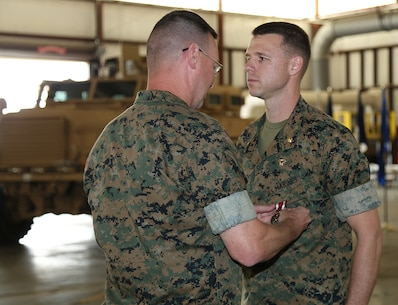 Maj. Jason J. Gates, right, s operations officer, Marine Force Storage Command,  receives the Meritorious Service Medal from Lt. Col. Timothy B. Egan, director, Fleet Storage Division-Albany, MFSC, during a ceremony held at the Building 1430 aboard Marine Corps Logistics Base Albany, Ga., April 19. Gates served 22 years in the Marine Corps.