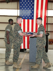 Maj. Jason J. Gates, right, operations officer, Marine Force Storage Command,  receives an American flag from Lt. Col. Timothy B. Egan, director, Fleet Storage Division-Albany, MFSC, during a ceremony held at the Building 1430 aboard Marine Corps Logistics Base Albany, Ga., April 19. Gates retired after 22 years of honorable service in the Marine Corps.