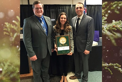Three people pose for picture, middle person holds award.