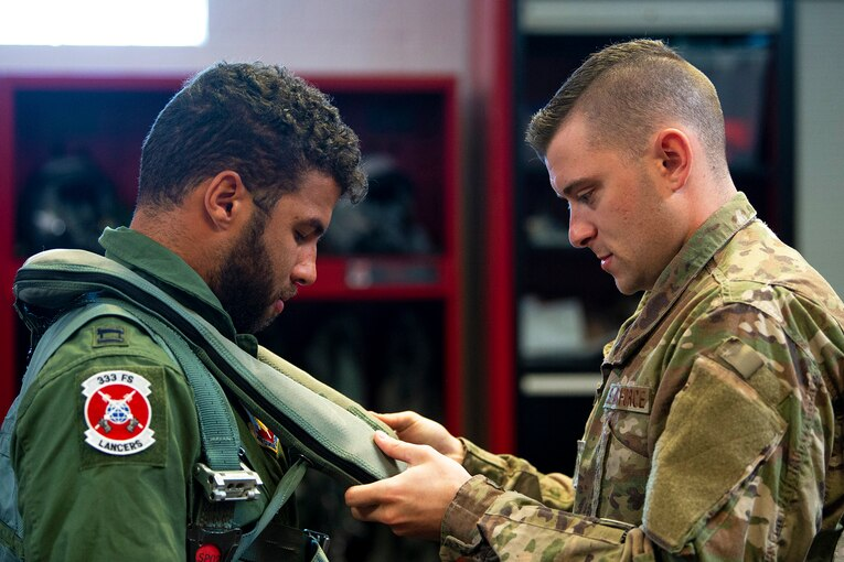 An airman adjusts a vest on a man wearing pilot's uniform.