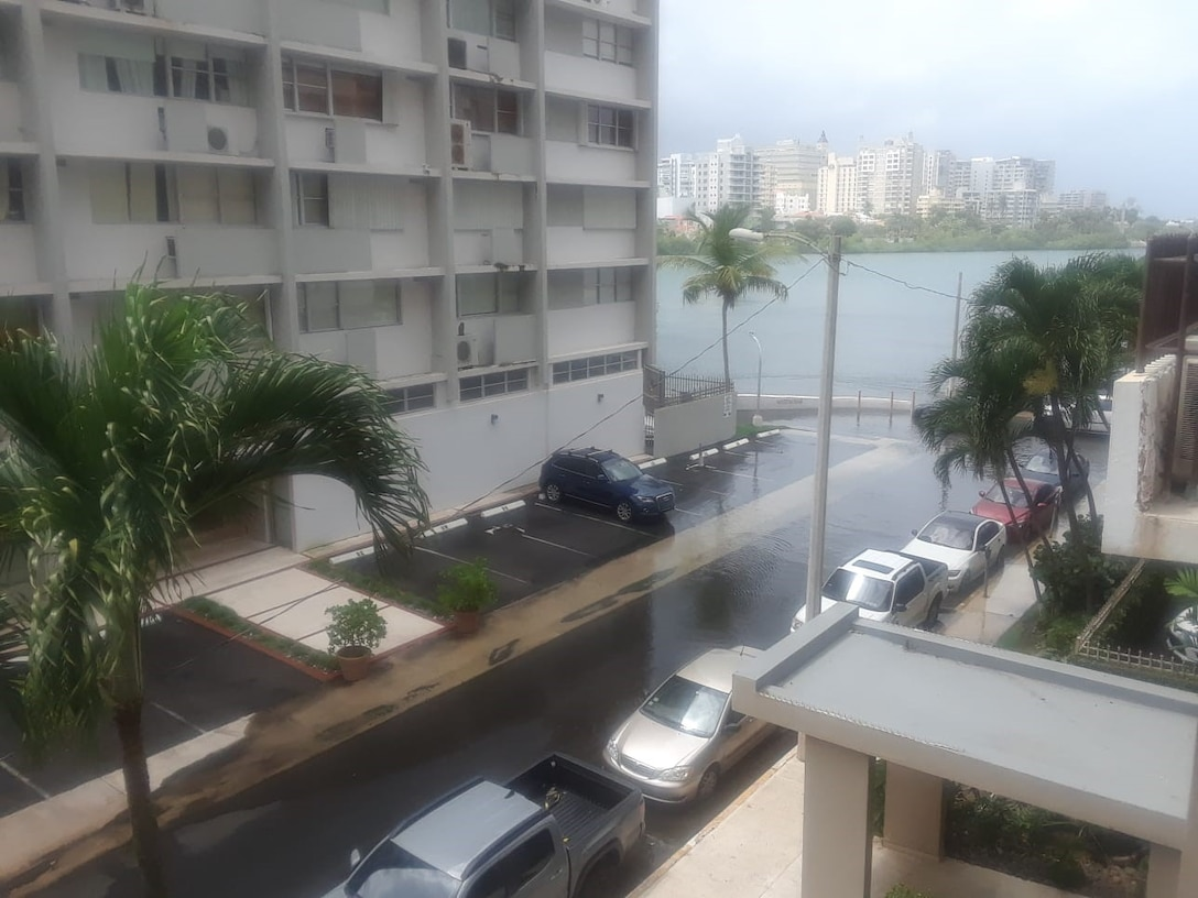 flooded street with cars in the street, building on the left and Condado lagoon on the background.