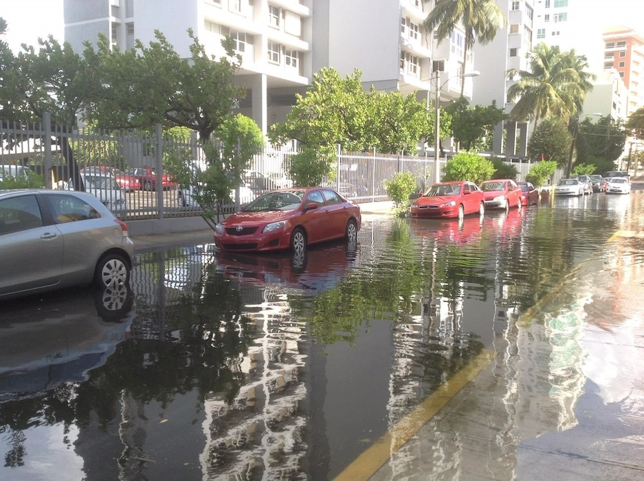 flooded street with cars and a building on the left