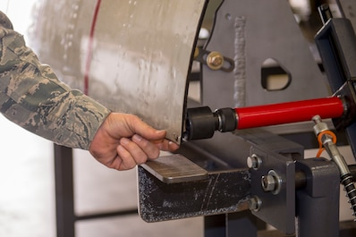 A U.S. Air Force sheet metal technician with the 116th Air Control Wing aircraft structural maintenance section, Georgia Air National Guard, shows how a hydraulic press on the newly-created cowling fixture table is capable of precision maintenance April 3, 2019, at Robins AFB, Ga.