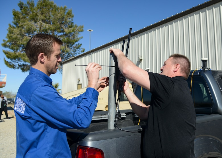 Technicians from Autonomous Solutions Inc. attach a radio antenna to a vehicle during a site survey to gather information needed to provide their autonomous services to the Precision Impact Range Area at Edwards Air Force Base, Calif., April 17. The collaboration between Team Edwards and ASI was born from the Air Force's AFWERX and Small Business Innovation Research program which allows a faster process for new and emerging technology companies to showcase their products to the Air Force. (U.S. Air Force photo by Giancarlo Casem)