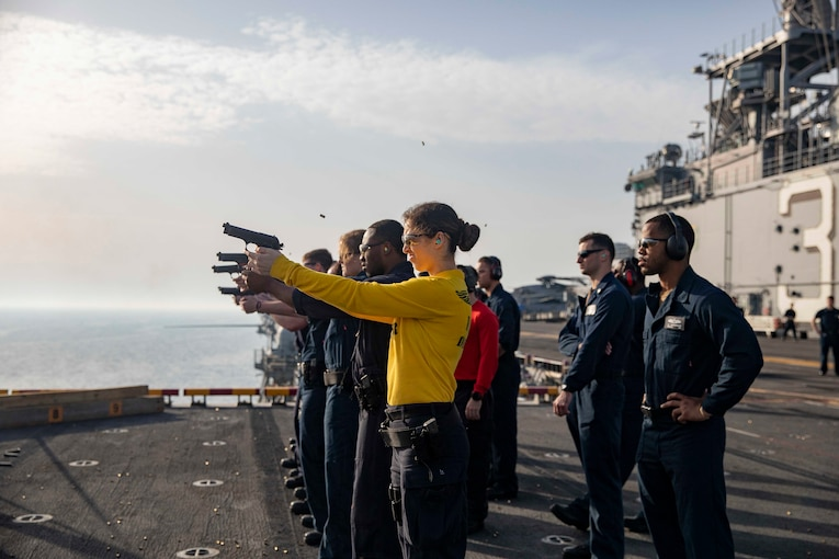 A female sailor in yellow and a line of sailors beside her fire pistols from a ship as instructors look on.