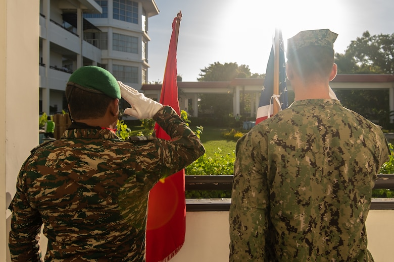 DILI, Timor-Leste (April 23, 2019) – Timor-Leste Defense Force Lt. Rufino Lima and U.S. Navy Hospital Corpsman Grayson Powell salute their respective ensigns during the Pacific Partnership 2019 opening ceremony for Timor-Leste. Pacific Partnership, now in its 14th iteration, is the largest annual multinational humanitarian assistance and disaster relief preparedness mission conducted in the Indo-Pacific. Each year the mission team works collectively with host and partner nations to enhance regional interoperability and disaster response capabilities, increase security and stability in the region, and foster new and enduring friendships in the Indo-Pacific.