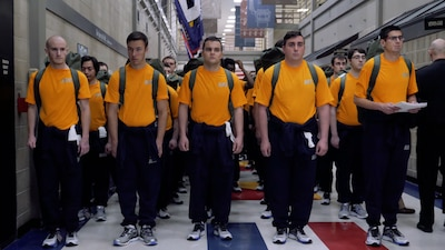 Recruits standing with backpacks in corridor