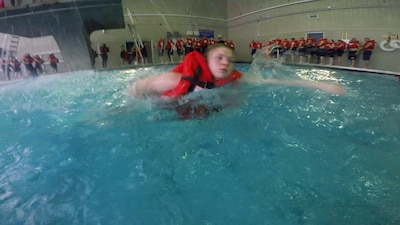 Recruits swimming with life preserve jacket in the pool