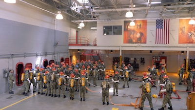 Recruits with fire fighting equipments on, learning how to handle the hose