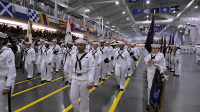 Boot Camp Graduation of Sailors marching in files with flags in the front