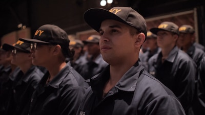 Recruits in their navy uniforms with caps listening