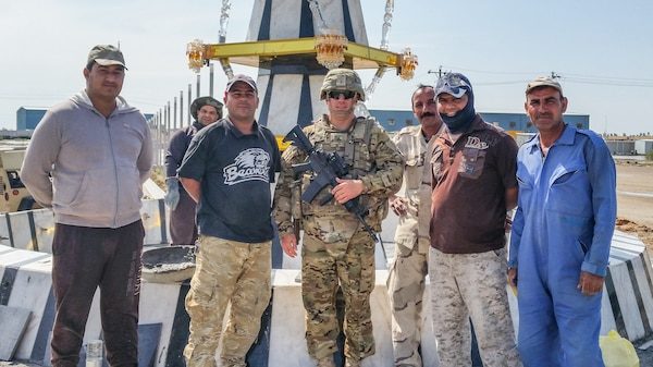 Staff Sgt. Bradley Owens, a combat medic with the West Virginia Army National Guard's (WVARNG) Company C, 2-104th General Support Aviation Battalion, poses with Iraqi nationals during a tour of duty in Taji, Iraq, in 2016. Owens recently was able to apply his 68W training to assist a driver whose vehicle had careened off an interstate overpass in Parkersburg, W.Va.