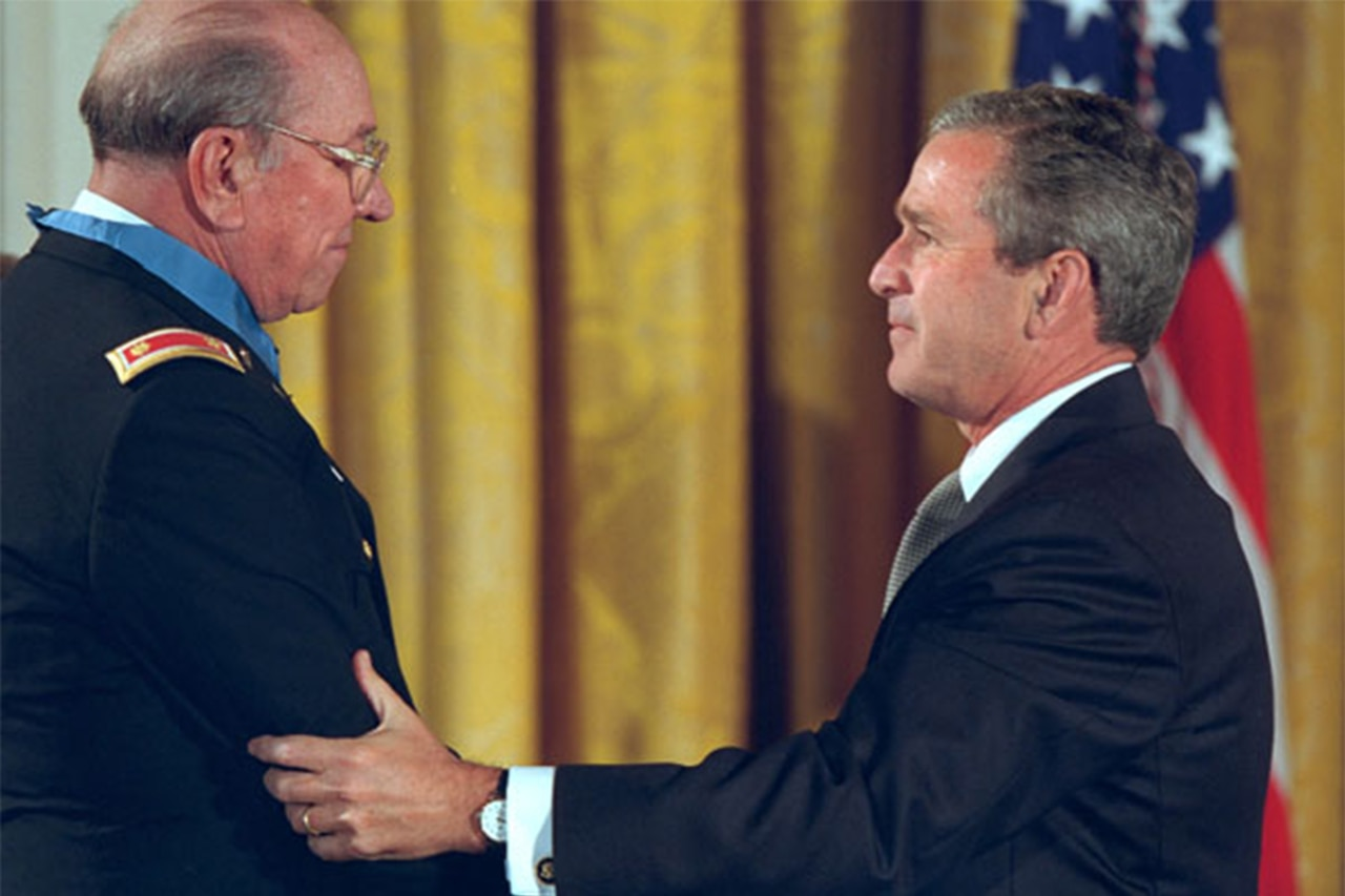 President George W. Bush holds the elbow of an older soldier wearing the Medal of Honor.