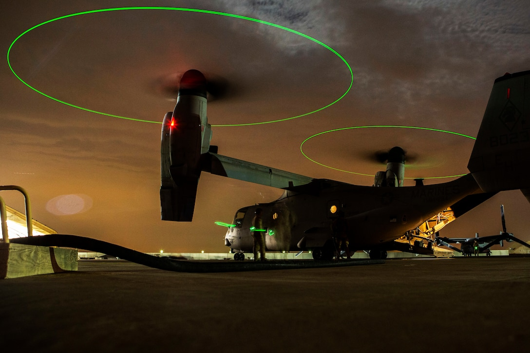 Two Marines check an Osprey at night as the rotors above them are outlined in green light.