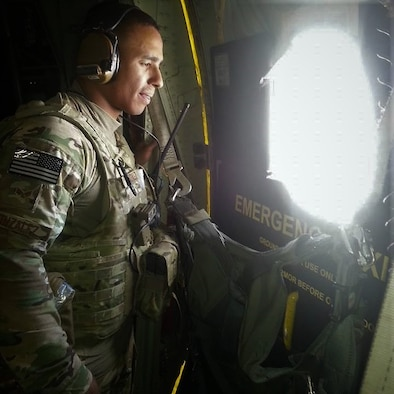 Tech. Sgt. Carlos Gonzalez looks out a while aboard a C-130 Hercules aircraft while deployed in 2016.