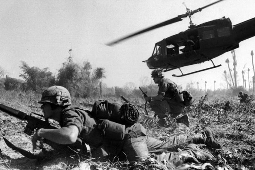 Two soldiers get in defensive positions on a field in Vietnam as a helicopter lifts into the air in the background.