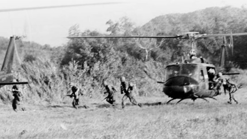 Several soldiers jump out of a helicopter in a field in Vietnam.