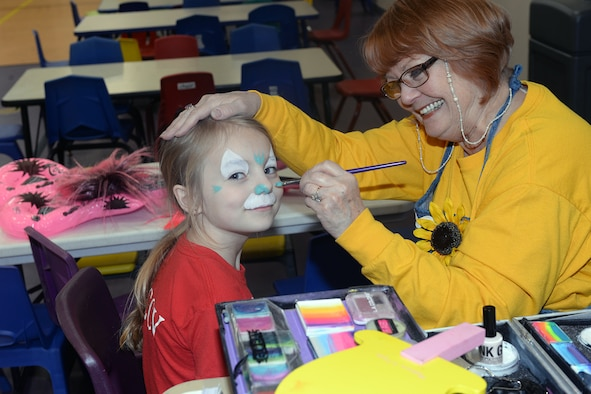 Ruth Merwald, Giggles the clown, paints a child's face April 9, 2019 at the Bellevue Lied Center, Nebraska. The 6th Annual Special Needs Fair also offered food and vendors. (U.S. Air Force photo by Kendra Williams)