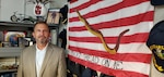 Man stands in office next to First Navy Jack flag.