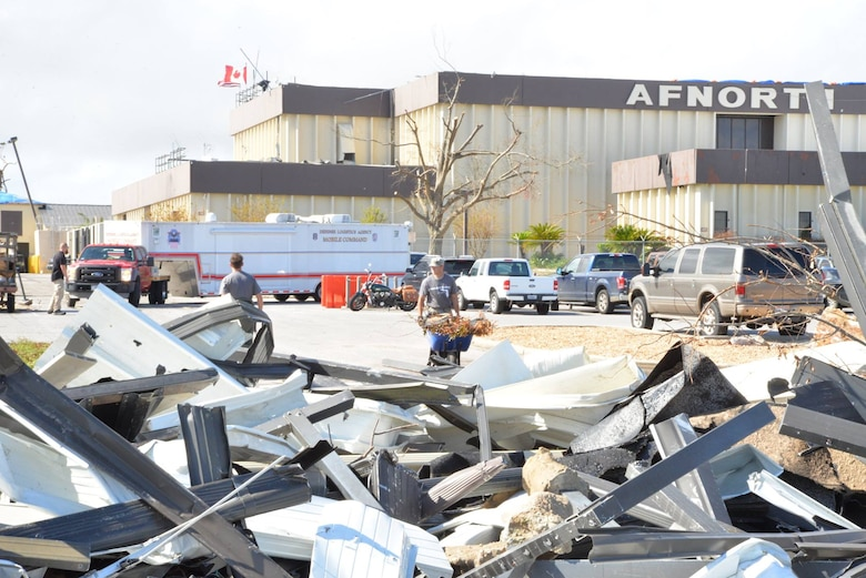 Members of the 601st Air Operations Center clean up debris outside the main building after being hit by Hurricane Michael, a category five storm that ravaged Tyndall Air Force Base, Fla., and the surrounding area, Bay County. The aggressive recovery effort to bring the Operation Noble Eagle mission back to Tyndall – 72 days – was highlighted in the Partridge-Slemon Award citation given to CONR as the 2018 recipient of the award. (U.S. Air National Guard photo by Maj. Andrew Scott)