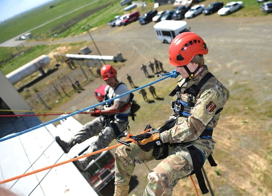 Gen. Maryanne Miller, Air Mobility Command commander, rappels down a building with the help of the 60th Civil Engineer Squadron as part of a tour of Travis Air Force Base, California, April 18, 2019. The tour served to highlight the relationship Travis' major command has with its bases' Airmen while also working to inspire innovative efforts among its respective squadrons. (U.S. Air Force photo by Airman 1st Class Christian Conrad)