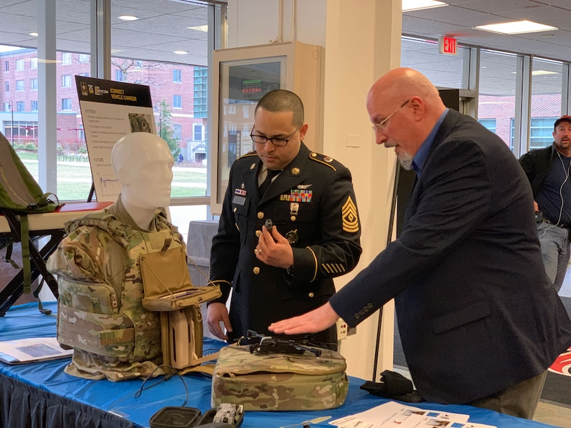 Army soldier talks with a man in a business suit at a table.