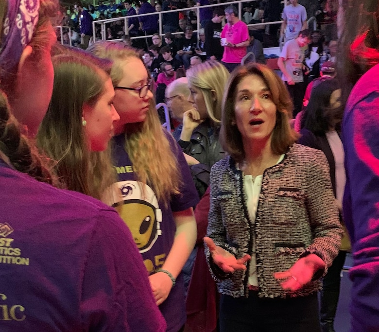 Woman in business suit talks with students.