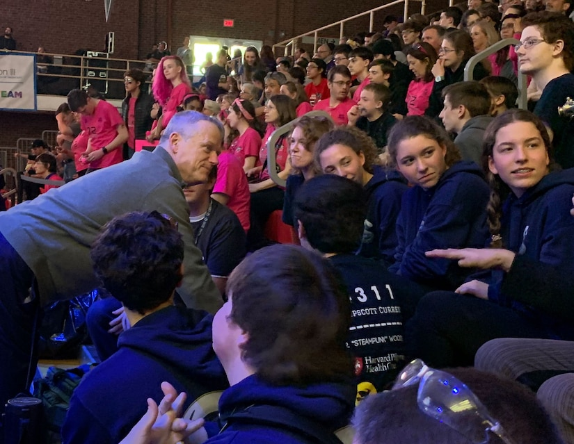 adult governor of Massachusetts talks with high school students on gym bleachers.