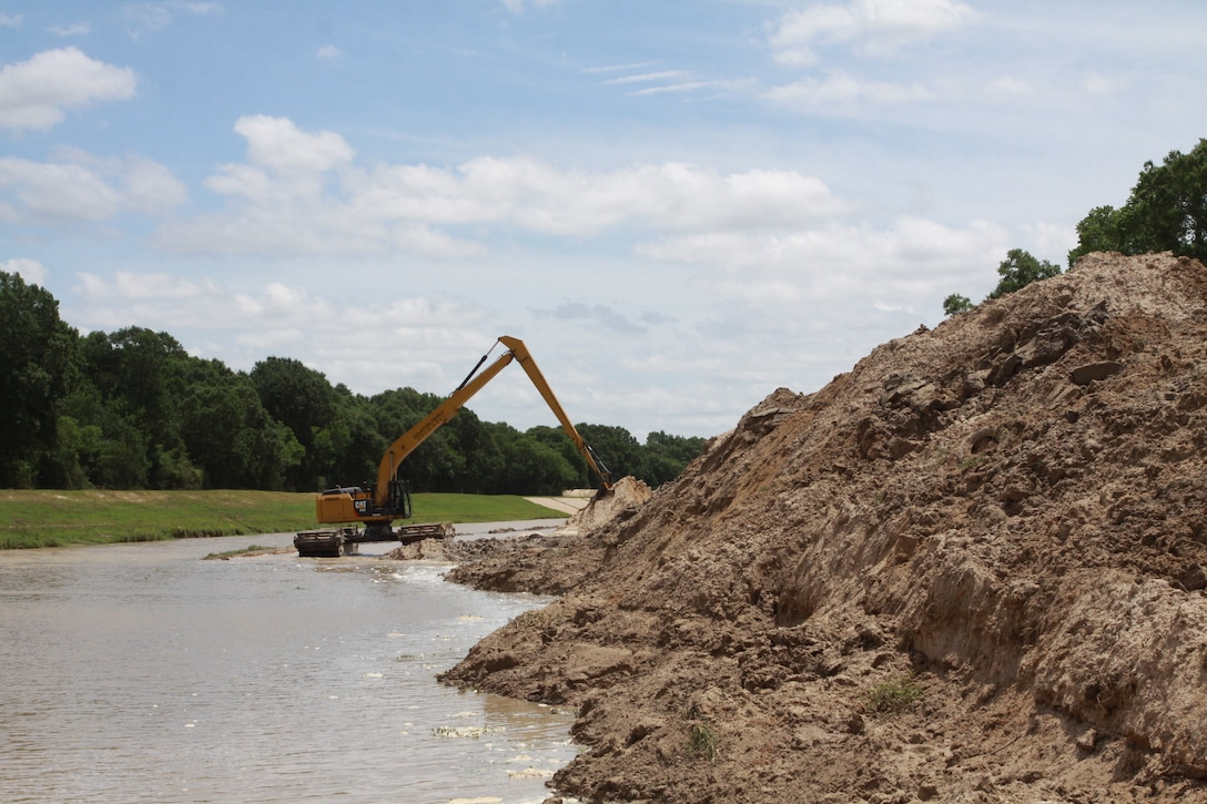 A pontoon based backhoe removes sediment from Buffalo Bayou in Fort Bend County.  The Galveston District permitted the Fort Bend County Flood Control District to remove silt in this 2.5 mile segment of Buffalo Bayou to increase water flow into Barker Reservoir.  Increased flow through this segment of Buffalo Bayou is calculated to reduce flooding upstream of the Barker Reservoir during heavy rain events.