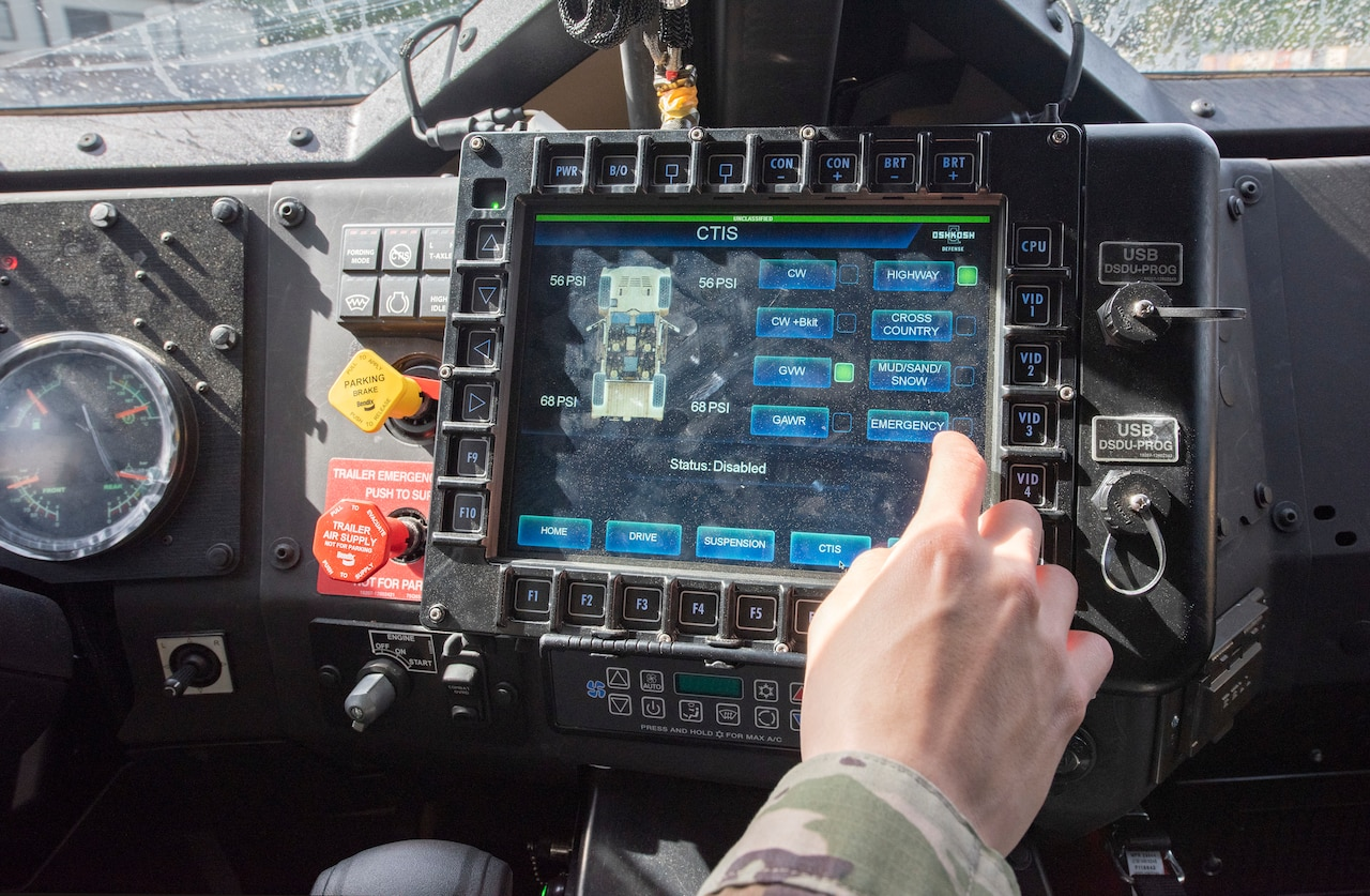 A soldier uses a touchscreen computer inside a joint light tactical vehicle.