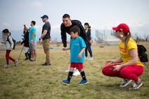 日本人の男の子がスプーンに卵を乗せて運んでいる側から海兵隊員が声援を送っています。