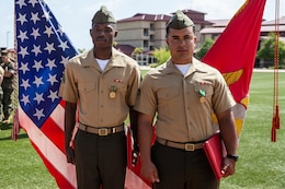 U.S. Marine Corps Cpl. Renzel Craft, left, and Cpl. Everton Porto, both heavy equipment mechanics with 1st Combat Engineer Battalion, 1st Marine Division, receive Navy and Marine Corps Achievement Medals during their Corporal Course graduation ceremony at Marine Corps Base Camp Pendleton, California, April 12, 2019. Craft and Porto received recognition for responding to an incident in the chow hall where a Marine was having a seizure.