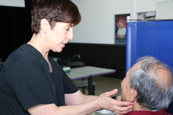 Tracey Fischer, left, a speech-language pathologist at Landstuhl Regional Medical Center, examines John Lucero for symptoms at the Ramstein Exchange during the Head and Neck Cancer Screen event Apr. 17. Providers from LRMC's Ear, Nose and Throat Clinic, Oral Surgery Clinic and Speech Pathology Department screened over 130 members of the Kaiserslautern Military Community for signs and symptoms of head and neck cancers.