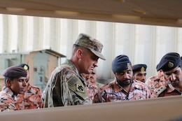 U.S. Army Sgt. 1st Class Chad Collins and Royal Army of Oman Soldiers inspect a tire after removing rim cover during the Heavy Equipment Transporter System Subject Matter Exchange II held at Sultan bin Safy Camp Shafa Oman, April 6-11, 2019.