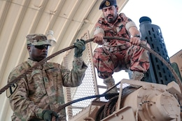 U.S. Army Sgt. 1st Class Josheph Davis assists Warrant Officer Sultan Salim Alaamari, Royal Army of Oman, with correcting a deficiency during the Heavy Equipment Transporter System Subject Matter Exchange II held at Sultan bin Safy Camp Shafa Oman, April 6-11, 2019.