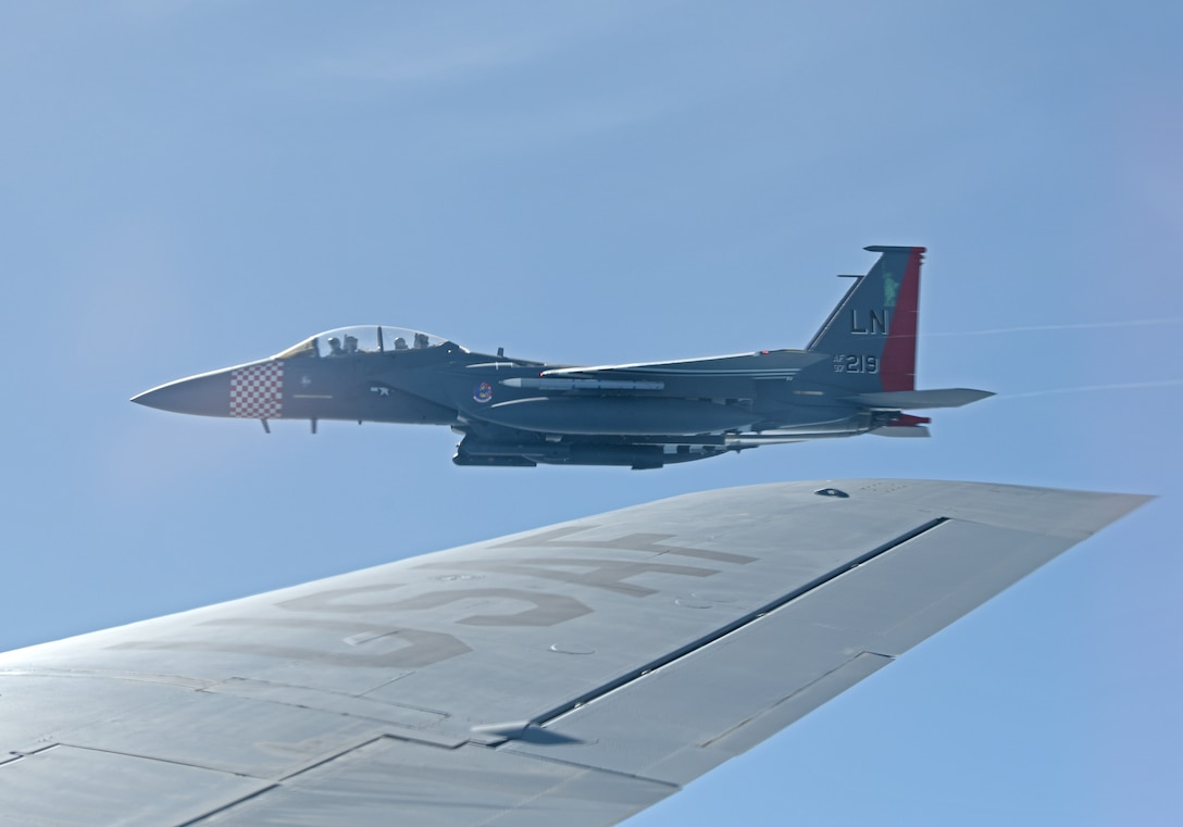"""An F-15E Strike Eagle assigned to the 48th Fighter Wing at RAF Lakenheath, England, painted in the heritage colors of its World War II P-47 Thunderbolt predecessor, flies next to a KC-135 Stratotanker of the 351st Air Refueling Squadron at RAF Mildenhall during the """"FURIOUS 48"""" readiness exercise over the skies of England, April 24, 2019. The exercise was designed to emphasize the importance of combat skills effectiveness training and test 100th ARW and 48th FW Airmen on their ability to survive and operate in wartime conditions. (U.S. Air Force photo by Airman 1st Class Brandon Esau)"""