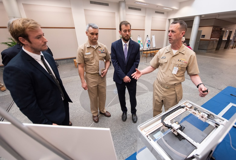Chief of Naval Operations Adm. John Richardson, right, chats with Naval Information Warfare Center Atlantic's Josh Heller, left, about using 3D printing to enable rapid solutions to materiel problems, as NIWC Atlantic Commanding Officer Capt. Wesley Sanders and Executive Officer Christopher Miller look on.