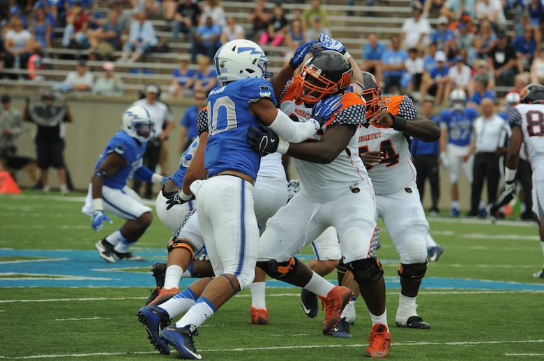 Air Force Academy defensive end Ryan Watson, left, pushes the left tackle back while trying to read the quarterback's play, during the Academy's 2015 win over Morgan State University. Watson played three seasons at defensive end and one at outside linebacker at the Air Force Academy, and registered eight sacks during his senior year. Now a program manager with AFLCMC, Watson has been invited to showcase his defensive skills at the Detroit Lions rookie minicamp, May 10-13. (U.S. Air Force photo/John Van Winkle).