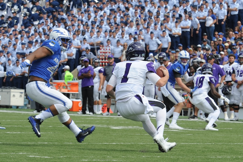 Air Force Academy defensive end Ryan Watson, left, disrupts a play and prepares to abruptly introduce himself to a quarterback, during the Academy's 2016 win over Abilene Christian University. Watson played three seasons at defensive end and one at outside linebacker at the Air Force Academy.  Now a program manager with AFLCMC, Watson has been invited to the Detroit Lions rookie minicamp, May 10-13. (U.S. Air Force photo/John Van Winkle)