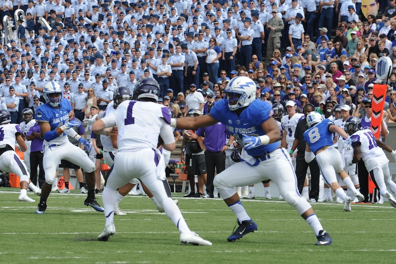 Air Force Academy Defensive End Ryan Watson, right, grabs Abilene Christian University quarterback Dallas Sealey for an eventual sack in this Sept. 3, 2016 game. Watson registered 14.5 sacks in four seasons at defensive end and outside linebacker at the Academy, and was offered a free agent contract with the Arizona Cardinals in 2017. Now a program manager with AFLCMC, Watson has been invited to the Detroit Lions rookie minicamp, May 10-13. (U.S. Air Force photo/John Van Winkle).