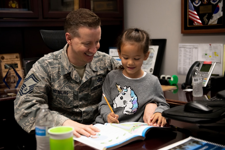 "U.S. Air Force Senior Master Sgt. Joshua Wessling, 33rd Fighter Wing wing staff superintendent, helps his daughter practice her writing and reading skills in his office Apr. 25, 2019, at Eglin Air Force Base, Florida. April 25th is ""National Take Our Sons and Daughters to Work Day"" and Wessling decided to show his son and daughter his daily life at work. (U.S. Air Force Photo by Senior Airman Cassidy Woody)"