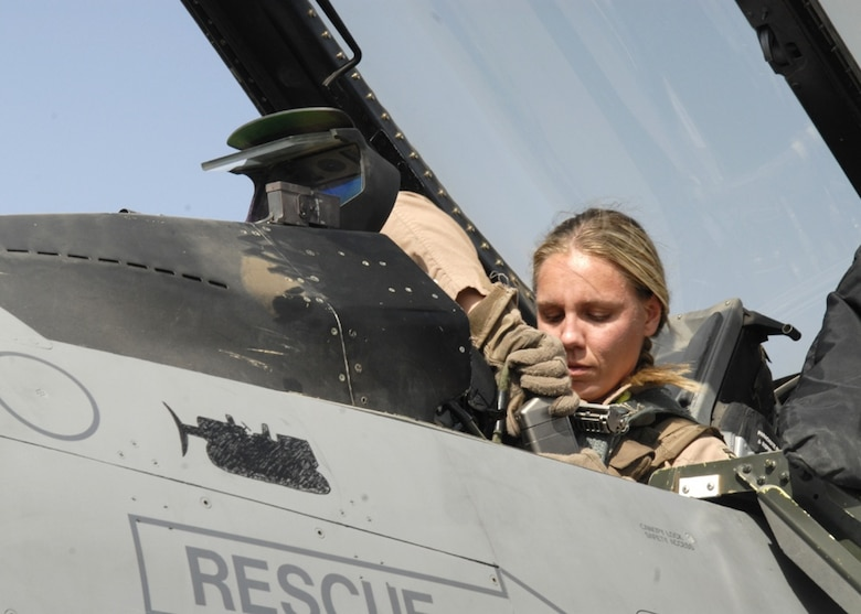 U.S. Air Force pilot Capt. Caroline Jensen, from the 4th Expeditionary Fighter Squadron, connects the communications receiver to her helmet ensuring she is in contact with personnel on the ground prior to taking off in an F-16 Fighting Falcon from Balad Air Base. Jensen is deployed from Hill Air Force Base, Utah. (U.S. Air Force Photo/Staff Sgt. Joshua Garcia, Released)