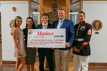 U.S. Marines with Marine Corps Recruiting Station Tampa present a check for the Marine Corps Naval Reserve Officer Training Corps Scholarship to Ricky Cooper, a native of Tampa, Florida, at Plant High School in Tampa, Florida, April 24, 2019.