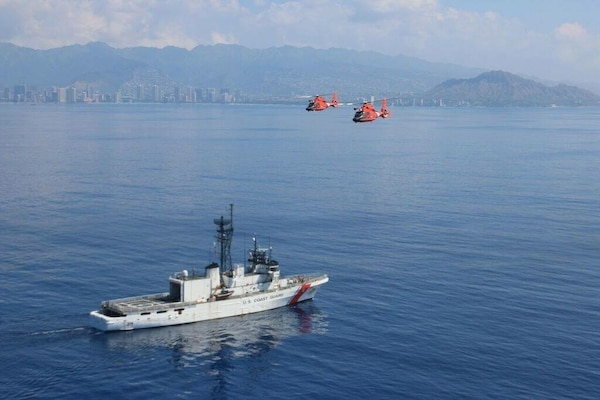 USCGC Alex Haley (WMEC 39) steams offshore of Honolulu as two MH-65 Dolphin helicopters from Coast Guard Air Station Barbers Point pass overhead March 4, 2016. The Alex Haley crew is in Hawaii for tailored ships training availability to assess the crew and the ship's readiness.